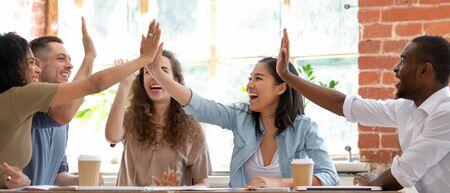 Los empresarios alegres multiculturales de imagen horizontal amplia sentados juntos en la reunión dando cinco gestos se sienten emocionados y felices, mostrando el espíritu de equipo, celebrando el concepto de logro de la meta de la victoria