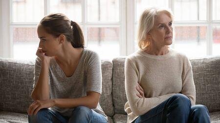 Dans une querelle, une mère âgée, une fille adulte, s'assoit sur un canapé séparément, ayant des conflits, un malentendu intergénérationnel, un petit-enfant adulte, une grand-mère difficile, de mauvaises relations concept de différentes générations Banque d'images