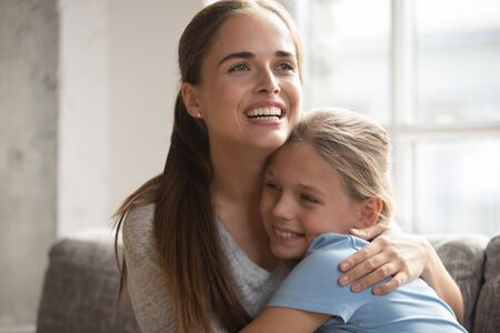 Loving young mother embracing little adorable daughter family sitting on couch, single mom and kid feeling happy hugging showing love deep caress devotion, adopted child and new mommy, custody concept