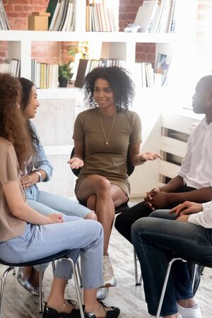 Vertical image diverse people sitting on chairs in circle listen psychologist telling personal stories at rehab group. Students gather together gain knowledge informal seminar study education concept Stockfoto
