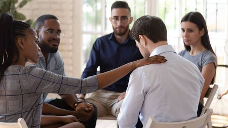 Rear view at upset man feel pain depression problem addiction get psychological support of counselor therapist coach diverse people friend group help patient during therapy counseling session concept. Stock Photo