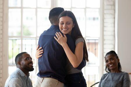 Sollevato riconciliato coppia sposata uomo e donna abbraccio sentirsi sani felici dare supporto psicologico empatia durante la sessione di terapia di gruppo, amici persone abbracciano aiutando nel concetto di riabilitazione