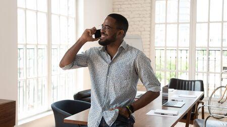 Fröhlicher afroamerikanischer Geschäftsmann, der in einem modernen Arbeitsplatz steht und telefoniert, lächelnder junger schwarzer Unternehmer-Startup-Besitzer, der auf dem Handy spricht, genießen mobile Gespräche im Kreativbüro