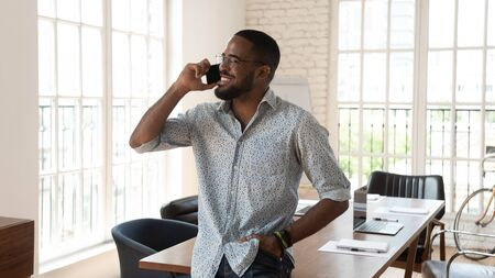 Happy african american businessman standing in modern work space talking on phone, smiling young black entrepreneur startup owner speak on cellphone enjoy mobile conversation in creative office