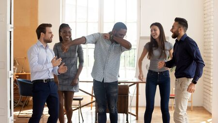 Happy funny motivated diverse business team people celebrating success win or enjoying corporate party in victory dance, positive friendly multiracial coworkers dancing in office having fun together