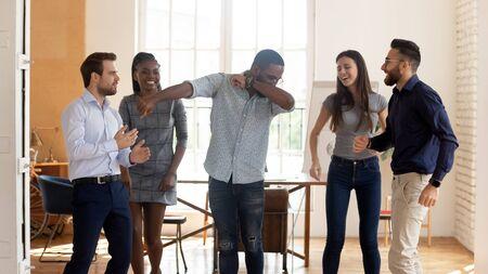Szczęśliwi zabawni zmotywowani różnorodni biznesowi ludzie świętujący sukces wygrywający lub cieszący się imprezą firmową w tańcu zwycięstwa, pozytywni przyjaźni wielorasowi współpracownicy tańczą w biurze, bawiąc się razem
