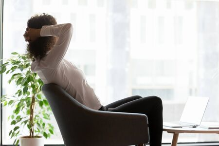Calm African American businesswoman relaxing in modern office during break, employee sitting in comfortable armchair with hands behind head, looking out window, dreaming about future, planning Foto de archivo