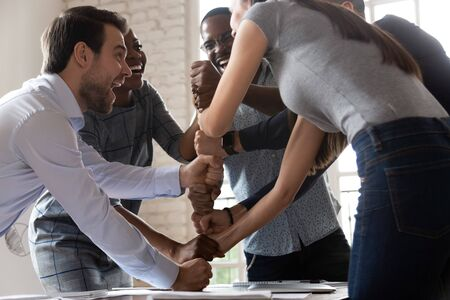 Overjoyed happy multiracial business team stacking fists motivated by corporate success, excited international work people group engaged in teambuilding celebrate victory good teamwork result concept