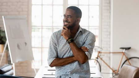 Dreamy happy african american black young business man looking away dreaming of good career think of successful startup strategy hoping for future opportunities goals stand in modern creative office.