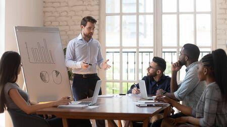 L'altoparlante dell'uomo d'affari presentatore manager maschio serio dà una presentazione aziendale a diversi gruppi di dipendenti al workshop di riunione dell'ufficio nella sala conferenze insegna al team al seminario di lezione di formazione aziendale. Archivio Fotografico