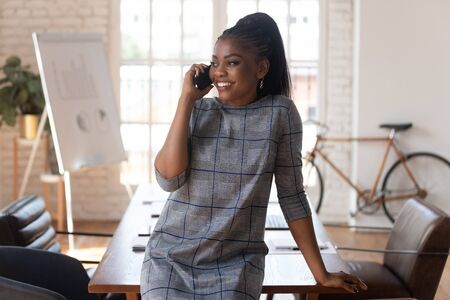 Smiling black businesswoman manager talking on phone making business call at work, happy female african american executive having mobile conversation consult client by mobile in modern office space