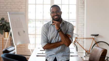 Happy african american businessman entrepreneur startup owner stand in modern office looking at camera, smiling young black designer creative occupation person posing in work space, business portrait Stock fotó