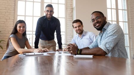 Happy international professional business people sit together at office table, smiling friendly diverse staff multiracial employees corporate workers group look at camera in boardroom, team portrait Stockfoto