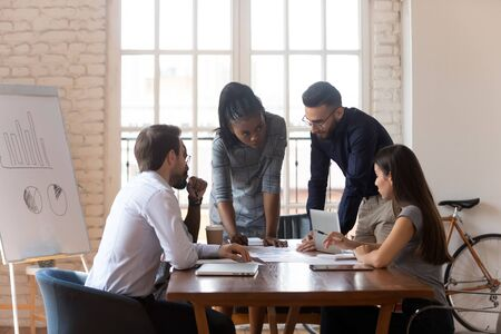 Multiracial business team diverse workers group cooperating brainstorm discussing paperwork share ideas on marketing plan working in teamwork at corporate meeting gather at office table in boardroom.