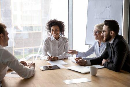 Diversi partner commerciali che discutono idee durante trattative di gruppo di successo, dipendenti sorridenti felici con il caposquadra afroamericano che lavora insieme al progetto, condividendo idee di avvio