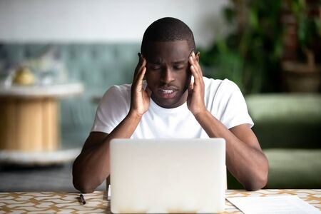 Unwell tired african American male student sit at desk with laptop massage temples suffer from headache, exhausted black man feel fatigue having migraine or blurry vision overworking at computer 免版税图像