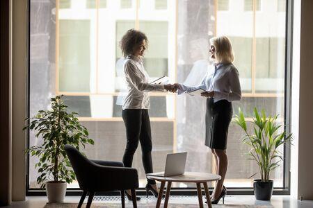 Femme d'affaires mûre serrant la main d'un partenaire commercial afro-américain lors d'une réunion, saluant, concluant un accord, poignée de main après des négociations fructueuses, debout près d'une grande fenêtre dans un bureau moderne