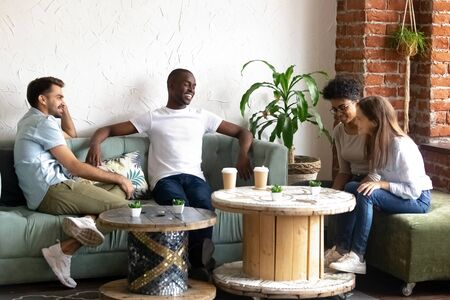 Smiling millennial girls talk get acquainted with multiracial young men hang out together in coffeeshop, happy multiethnic people sit in caf have fun introducing chatting. Acquaintance concept