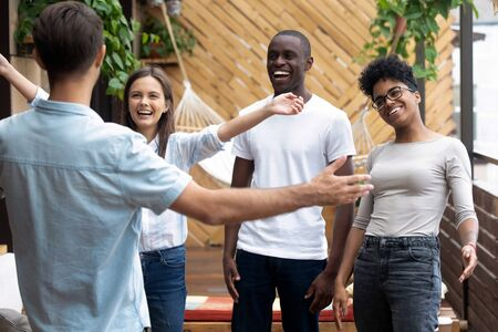 Overjoyed smiling multiracial millennial friends hug embrace meeting young man colleague in caf , excited happy diverse young people laugh hang out together greeting pal at casual gathering