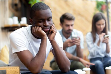 Unhappy thoughtful african American male outcast or loner sit aside feel sad and hurt lack friends, pensive black biracial millennial guy thinking considering relationships or communication problems