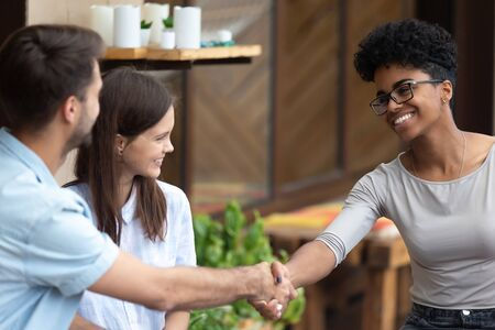 Smiling black female consultant shake hand with young couple clients meeting for talk in caf , happy millennial husband and wife handshake greeting architect or designer. Introduction concept