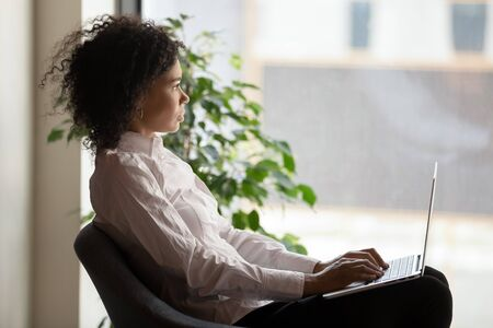 Thoughtful African American businesswoman looking out window, pondering online project, dreaming about future, pensive employee using laptop, sitting in comfortable armchair in modern office