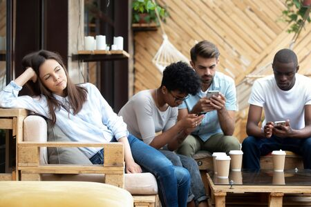 Unhappy millennial girl sit alone aside feel bored at group meeting with friends in caf , diverse young people busy using smartphones addicted to gadgets, annoyed female lack communication Imagens