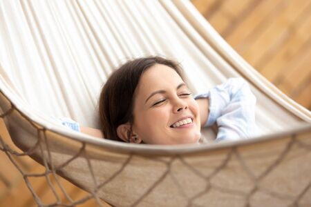 Smiling millennial girl relax in hammock with eyes closed enjoy sunny day, happy young caucasian woman rest laughing lying in hanging bed hands over head feel overjoyed with weekend or vacation