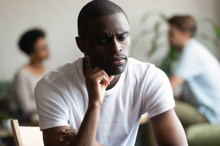 Unhappy african American millennial guy sit alone in coffeeshop thinking lack friends, upset sad biracial male outcast or loner feel offended hurt pondering having communication problem 版權商用圖片