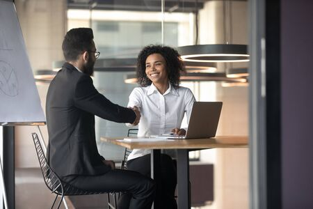 Smiling African American businesswoman shaking hand of business partner, friendly manager greeting client at meeting in boardroom, hr handshaking aspirant, good first impression, successful interview Фото со стока - 129153397