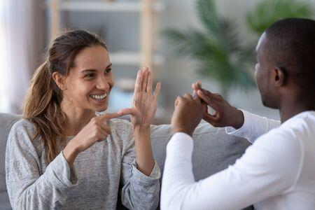Uśmiechnięta para o mieszanym pochodzeniu etnicznym lub międzyrasowi przyjaciele rozmawiający językiem migowego palca, szczęśliwa dwójka głuchoniemych i niedosłyszących osób z upośledzeniem słuchu komunikujących się w domu siedzą na kanapie pokazując gesty rąk