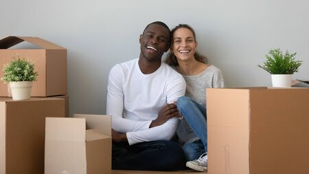 Happy african mixed race ethnicity couple first time home buyers looking at camera sit on floor in new home with boxes, smiling man and woman on moving day, relocation, mortgage concept, portrait