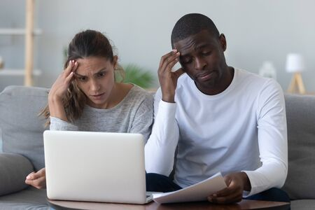Shocked worried young mixed race couple calculate bills pay online on laptop upset about financial problem high taxes expenses, interracial family stressed about paperwork unpaid bank debt bankruptcy