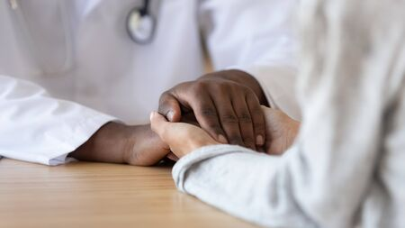 Grateful female patient holding hands of black male doctor thank for disease recovery therapy, support in miscarriage infertility treatment, hope support sympathy in medical health care close up view Stockfoto