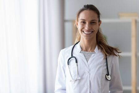 Smiling young mixed race female professional doctor wear white medical uniform with stethoscope looking at camera, happy friendly woman general practitioner nurse posing in hospital office, portrait