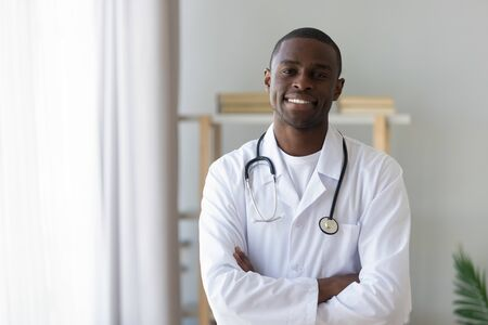 Smiling male african american professional young doctor stand arms crossed wear medical uniform looking at camera, happy confident black man general practitioner with stethoscope in office, portrait Stock fotó