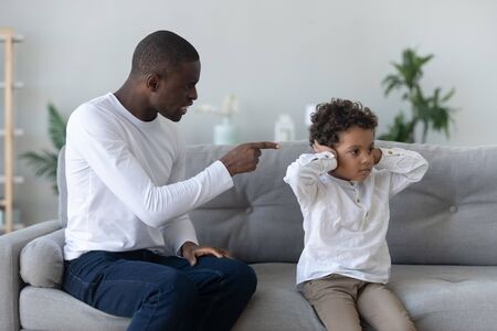 Angry single black father scolding stubborn fussy little african son closing ears not listening ignoring dad punish small mixed race kid boy for bad behavior, parent and child family conflict concept Stock Photo