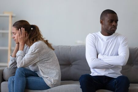 Unhappy mixed race ethnicity young couple sit separate turn back on sofa avoid talk after fight conflict, interracial upset husband and wife think of divorce, regret mistake sad in bad relationship