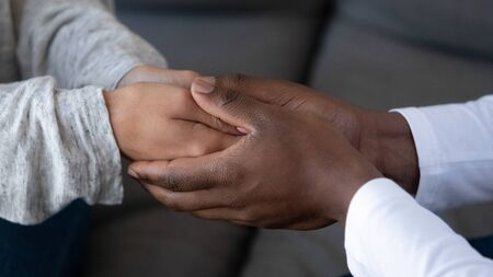 Close up view of african black man husband holding hand of white woman wife give support in marriage show compassion hope in relationship, comfort care of friend in mixed race family couple concept