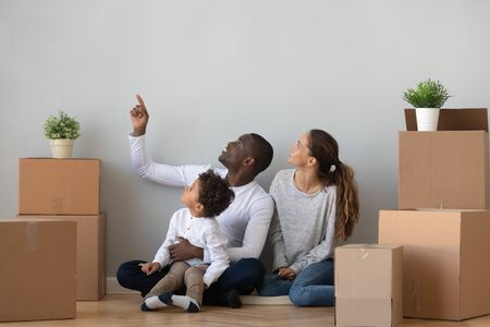 Happy african mixed race ethnicity family discuss new home renovation sit on floor relocating in own apartment with boxes, parents and cute child son talk enjoy moving day mortgage investment concept