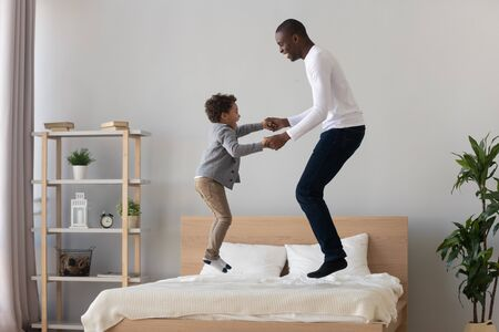 Happy active black father and cute small mixed race kid son holding hand jumping on bed mattress, carefree african american family dad with little child boy having fun laughing in bedroom together Stok Fotoğraf