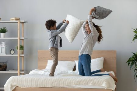 Lustige glückliche afrikanische Mischrasse-Familienmutter und kleiner süßer Sohn, die eine lustige Kissenschlacht auf dem Bett haben, junge Mutter lacht, die lustiges Spiel spielt, genießen Freizeitaktivitäten mit kleinen Kinderjungen im Schlafzimmer