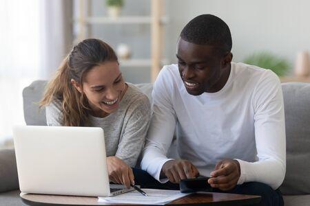 Feliz pareja joven de raza mixta calcular facturas domésticas tasa hipotecaria pago de préstamos bancarios en casa, sonriendo planificación familiar interracial presupuesto administrar gastos domésticos papeleo usar calculadora portátil
