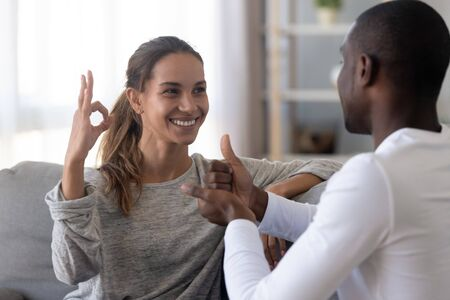 Happy mixed race deaf and dumb couple using sign language for communication at home sit on sofa, interracial hearing impaired disabled man and woman showing hand gestures as finger speech concept