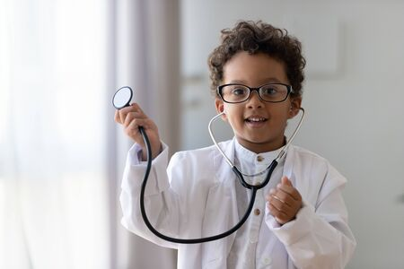 Cute small african american kid boy wear medical uniform glasses holding stethoscope playing doctor, happy funny little mixed race preschool child pretending pediatrician looking at camera, portrait