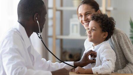 Afrikanischer männlicher Kinderarzt hält Stethoskop-Untersuchung Kind Junge Patient besucht Arzt mit Mutter, schwarzer Kinderarzt überprüft Herzlunge des Kindes führt pädiatrische Untersuchung im Krankenhauskonzept für die medizinische Versorgung von Kindern durch