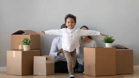 Happy cute african child boy running in new apartment looking at camera on moving day, excited little kid son exploring house with parents boxes on background, children and family mortgage relocation