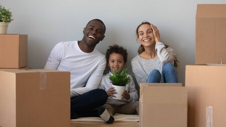 Happy african mixed race ethnicity family looking at camera sit on floor in new home with boxes, smiling parents and little child son on moving day, relocation, renovation, mortgage concept, portrait Banque d'images