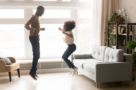 Happy African American father in glasses and little daughter jumping together, playing in living room at home, smiling dad with preschool girl having fun on weekend, family funny activity concept