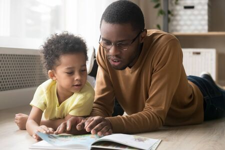 African American father in glasses and toddler son reading book together, lying on warm floor at home, black dad close up reading aloud fairy tale to adorable child, education, family weekend Stock Photo